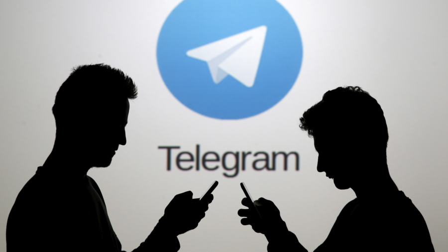 Two men pose with smartphones in front of a screen showing the Telegram logo in this picture illustration taken in Zenica, Bosnia and Herzegovina November 18, 2015. The mobile messaging service Telegram, created by the exiled founder of Russia's most popular social network site, has emerged as an important new promotional and recruitment platform for Islamic State. The service, set up two years ago, has caught on in many corners of the globe as an ultra-secure way to quickly upload and share videos, texts and voice messages. It counts 60 million active users around the world. Picture taken November 18.     REUTERS/Dado Ruvic - RTS7W3T